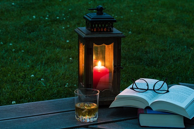 Early evening outdoors with a lit latern, a drink, an open book and a pair of eyeglasses.